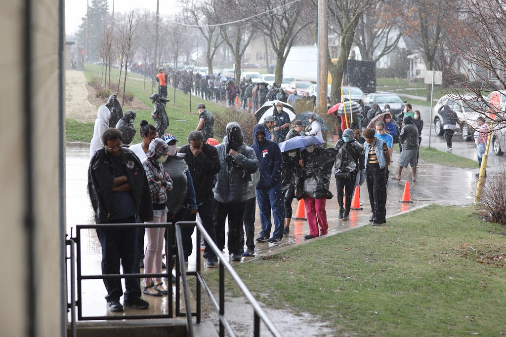 A long line of people in Wisconsin standing in the rain waiting to vote.